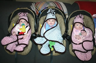 triplets wearing Cuddlebabe infant wraps